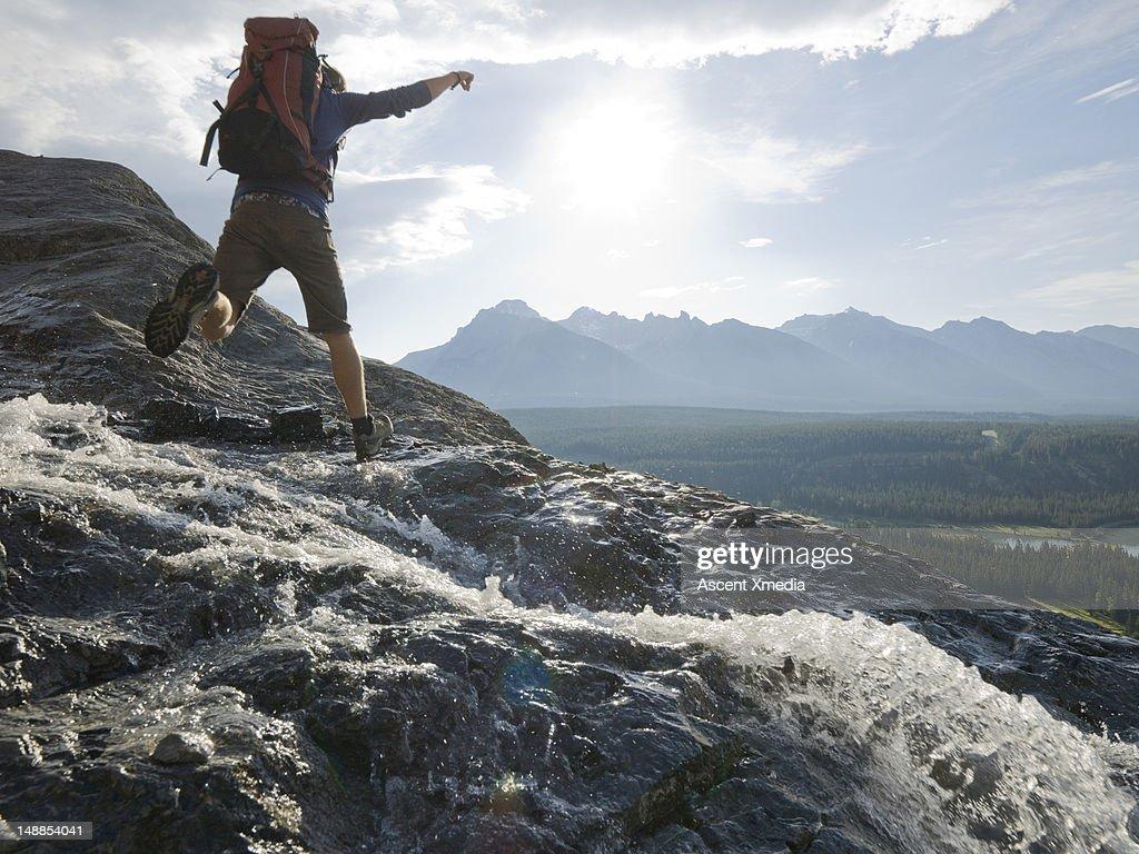 Hiker jumps creek on rock ledge, mtns below : Stock Photo