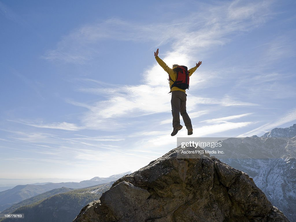 Hiker jumps for joy above rock, mountains : Stock Photo