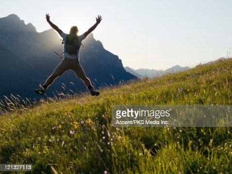 Hiker jumps for joy in mountain meadow : Stock Photo