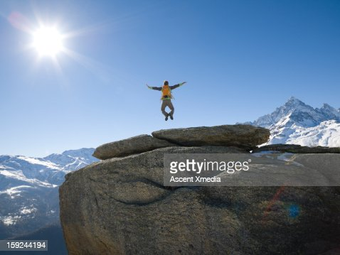 Hiker jumps into mid-air from rock summit,arms out : Stock Photo