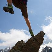 Hiker jumps overhead from rock buttress, mtns