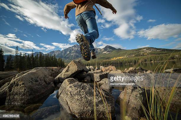 Hiker jumps rock to rock in mountain lake. Low angle