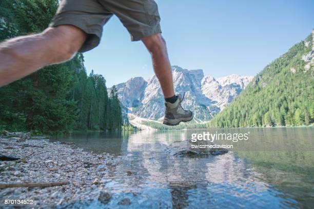 Hiker jumps rock to rock on mountain lake, Lago di Braies, Italy