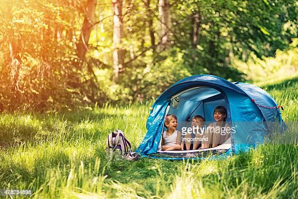 Enfants assis dans une tente de randonnée dans la forêt.