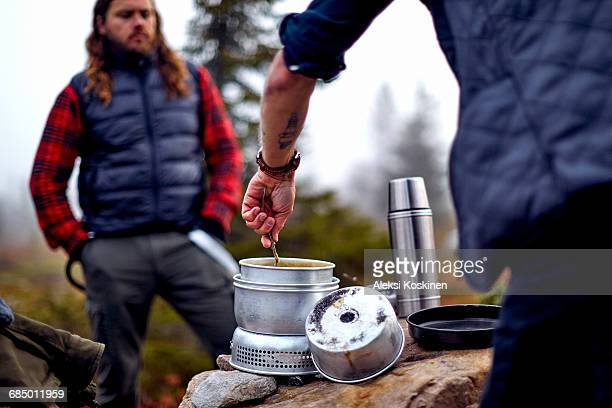 Hiker looking at friend cooking, Sarkitunturi, Lapland, Finland