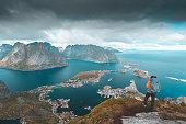 Hiker looking at the View of Reine in Lofoten, Norway