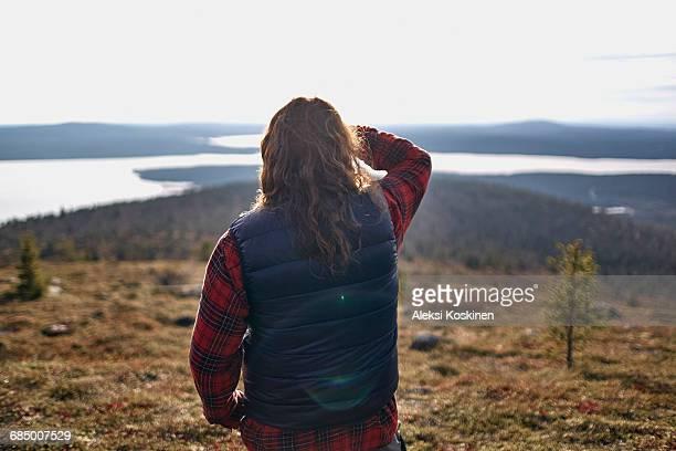Hiker looking out to lake, Keimiotunturi, Lapland, Finland