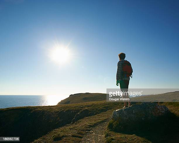 Hiker looking out to sea from Atlantic coastline.