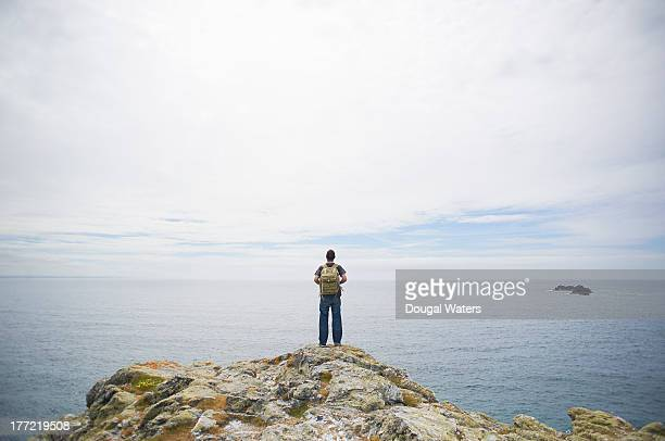 Hiker looking out to sea from cliff top.