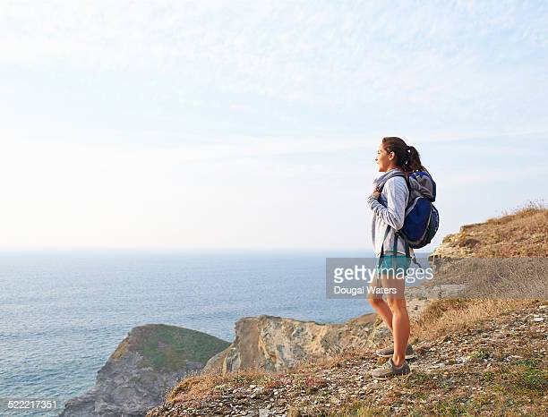 Hiker looking out toward sea from cliff top.
