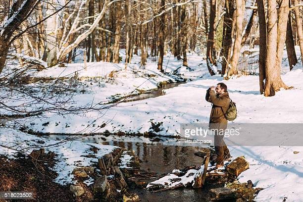Hiker Looking Through Binoculars In A Sunny Winter Forest