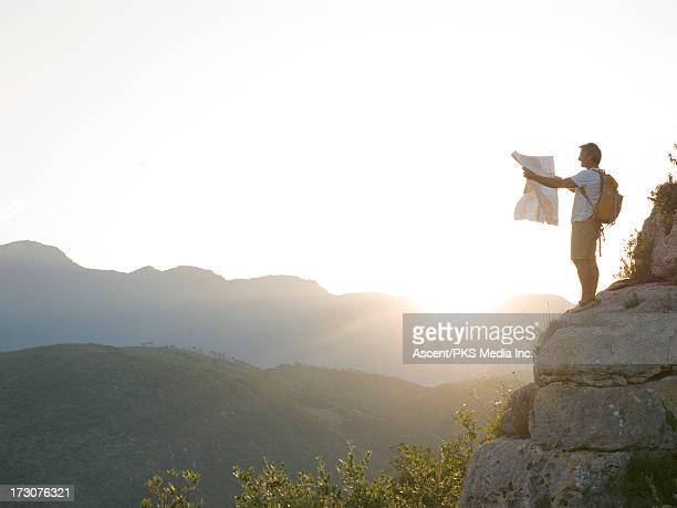 Hiker looks at map from rock buttress, sunrise