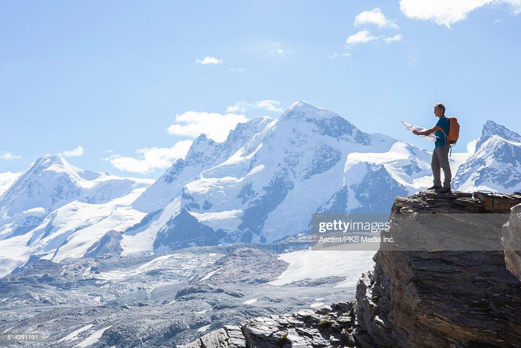 Hiker looks at map on mountain ridge crest