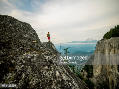 Hiker looks off from mountain ridge crest