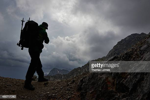 A hiker looks to dark clouds on his way to the mountain 'Lamsenspitze' at the Karwendel region on June 13 2014 near Vomp Austria The Karwendel is the...