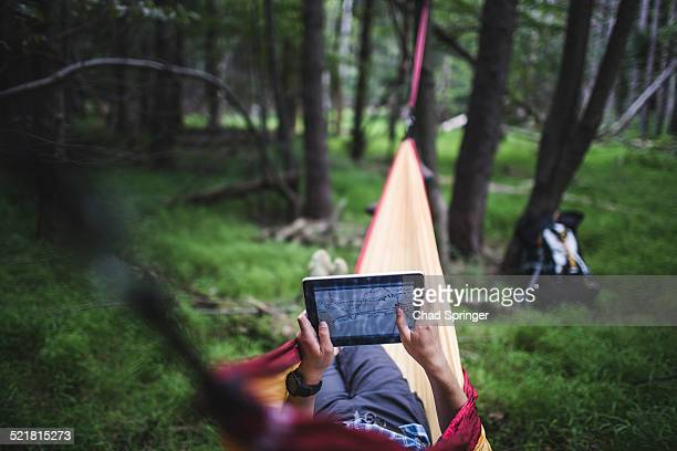 Hiker lying in hammock in forest looking at map on digital tablet