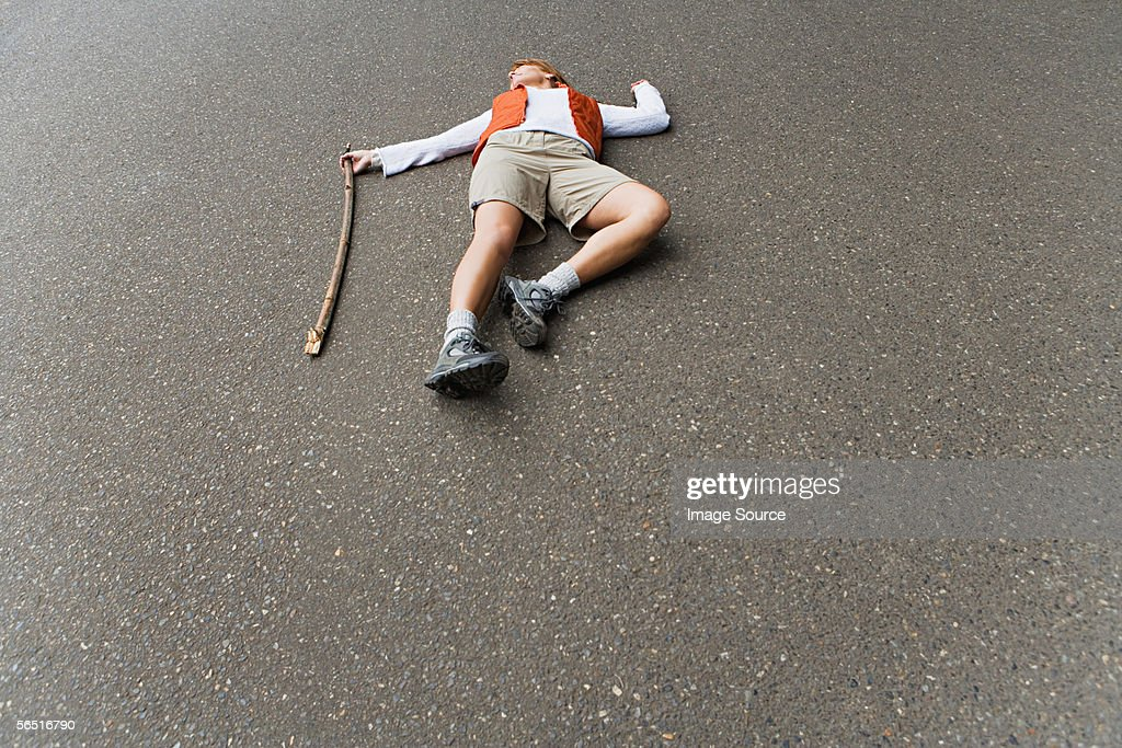 Hiker lying in the road : Stock Photo