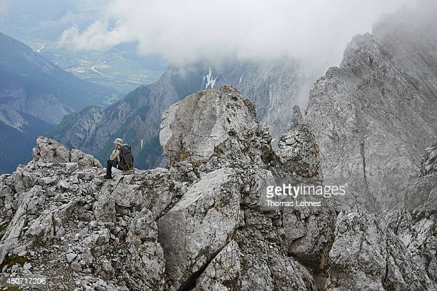 A hiker makes a break and looks to the 'Inntal' on his way to the mountain 'Hochnissl' at the Karwendel region on June 13 2014 near Vomp Austria The...