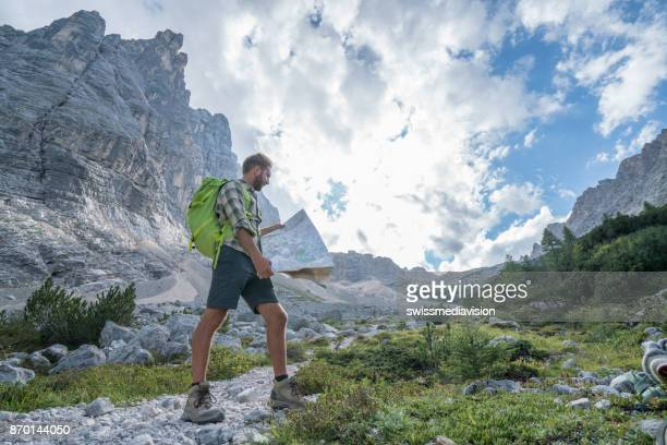 Hiker male consulting trail map, Dolomites, Italy