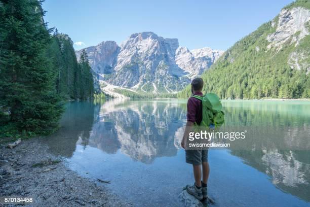 Hiker male contemplating beautiful mountain lake, Italy