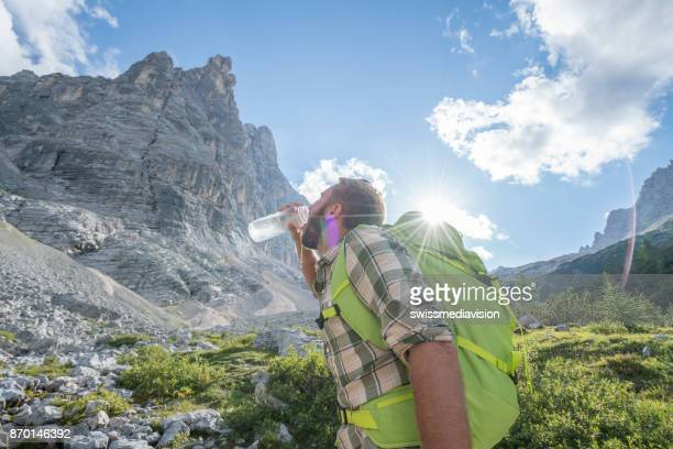 Hiker male drinking on mountain trail, Dolomites, Italy
