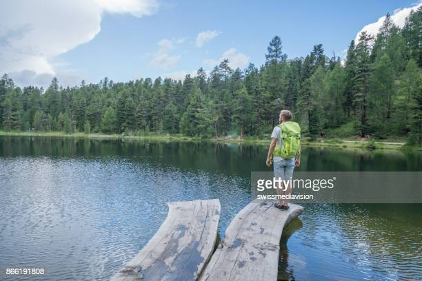 Hiker man enjoying nature from lake pier, Switzerland