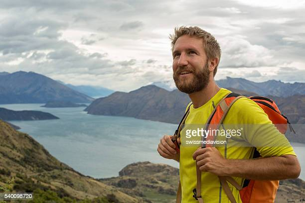 Hiker man stands on mountain top and looks at view