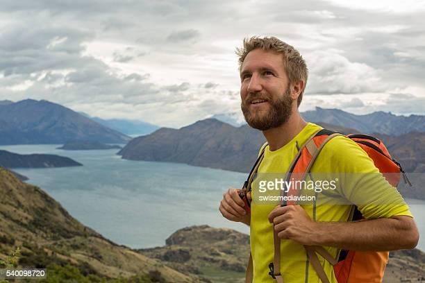 Randonneur homme se dresse au sommet de la montagne et est de vue