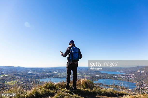 Hiker man using smartphone on mountain top