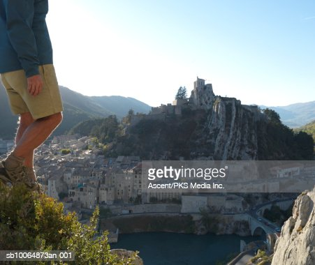 Hiker moving down hill, townscape in background, low section : Stock Photo