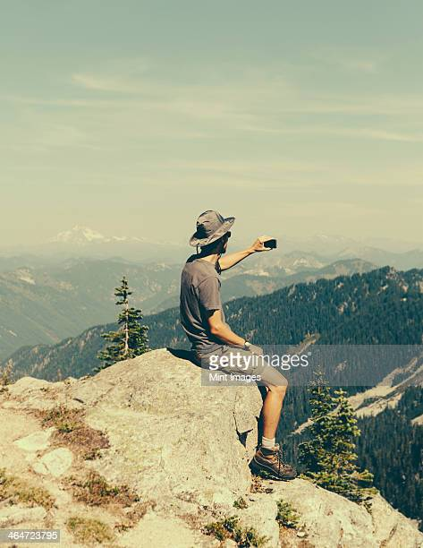 A hiker on a mountain summit,holding a smart phone,at the top of Surprise Mountain,in the Alpine Lakes Wilderness,in Mount Baker-Snoqualmie National Forest.