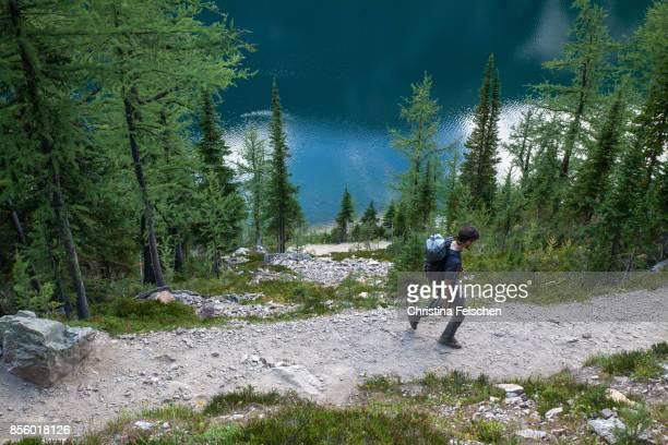 Hiker on a trail along Lake Agnes, Banff National Park, Canada
