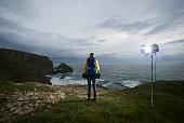 Hiker on cliff top under spotlight.