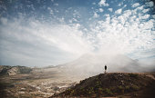 Hiker on hill overlooking Mount St. Helens