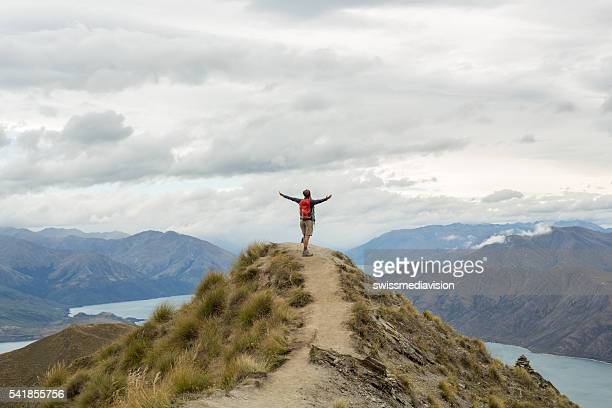 Hiker on mountain top, celebrates achievement