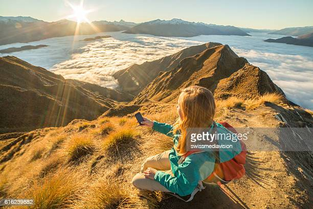 Hiker on mountain top using mobile phone