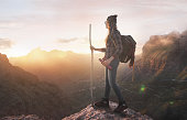 Hiker on moutain summit, sunset