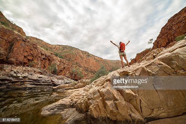 Hiker on rock arms outstretched