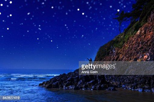 Hiker on rocks at Cannon Beach at night, stars