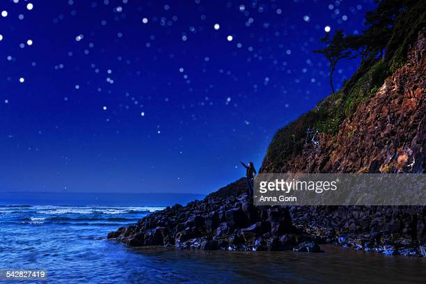 Hiker on rocks at Cannon Beach at night, stars