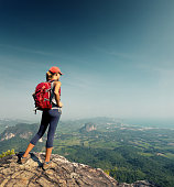 Lady hiker with backpack standing on top of the mountain