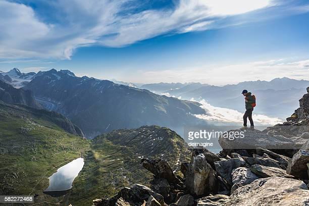 Hiker on top looks mountain panorama