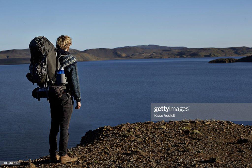 Hiker overlooking mountain lake : Stock Photo