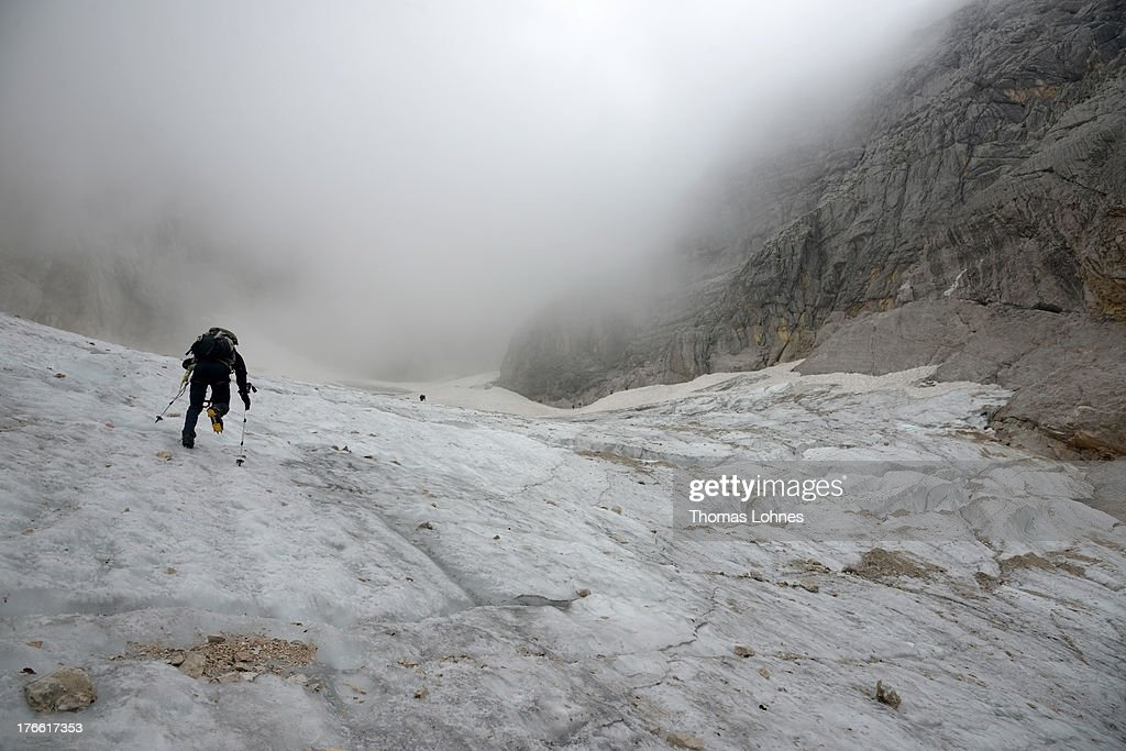 A hiker passes the glacier on the way to Germany's highest mountain Zugspitze (2.962 meter) in the Alps near the village of Garmisch-Partenkirchen on August 14, 2013 in Garmisch-Partenkirchen, Germany.