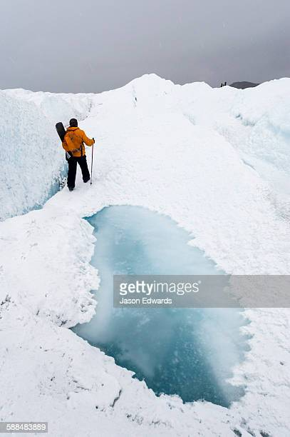 A hiker passing between a dangerous crevasse and a melt pond on the Greenland Ice Shelf.