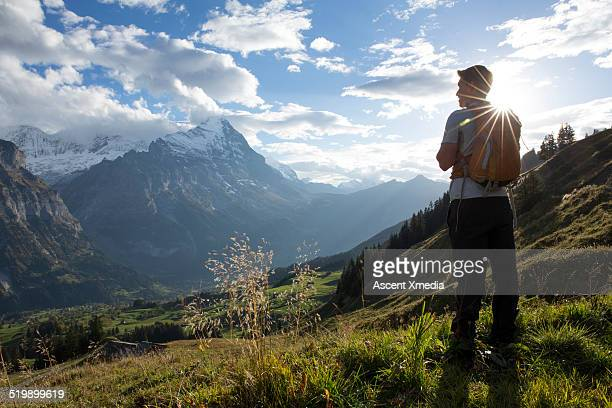 Hiker pauses in meadow above mountain valley