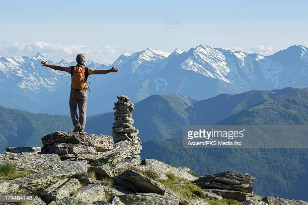 Hiker pauses on mountain summit, arms out