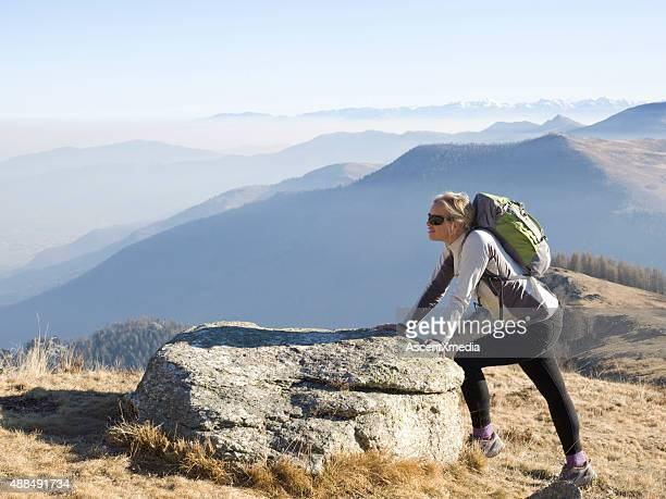 Hiker pauses to stretch by rock above mountains