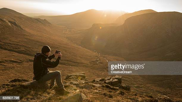 Hiker photographing Mourne Mountains, Northern Ireland