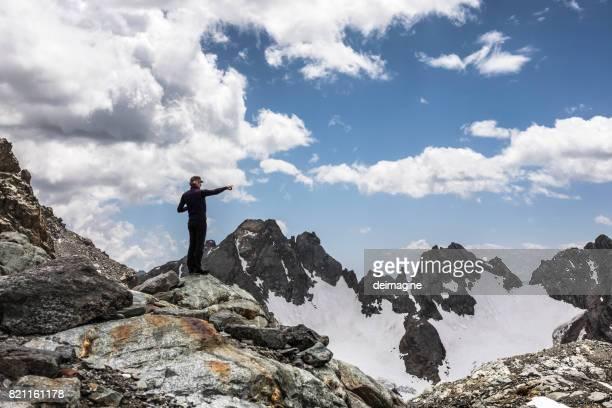 Hiker pointing mountain range
